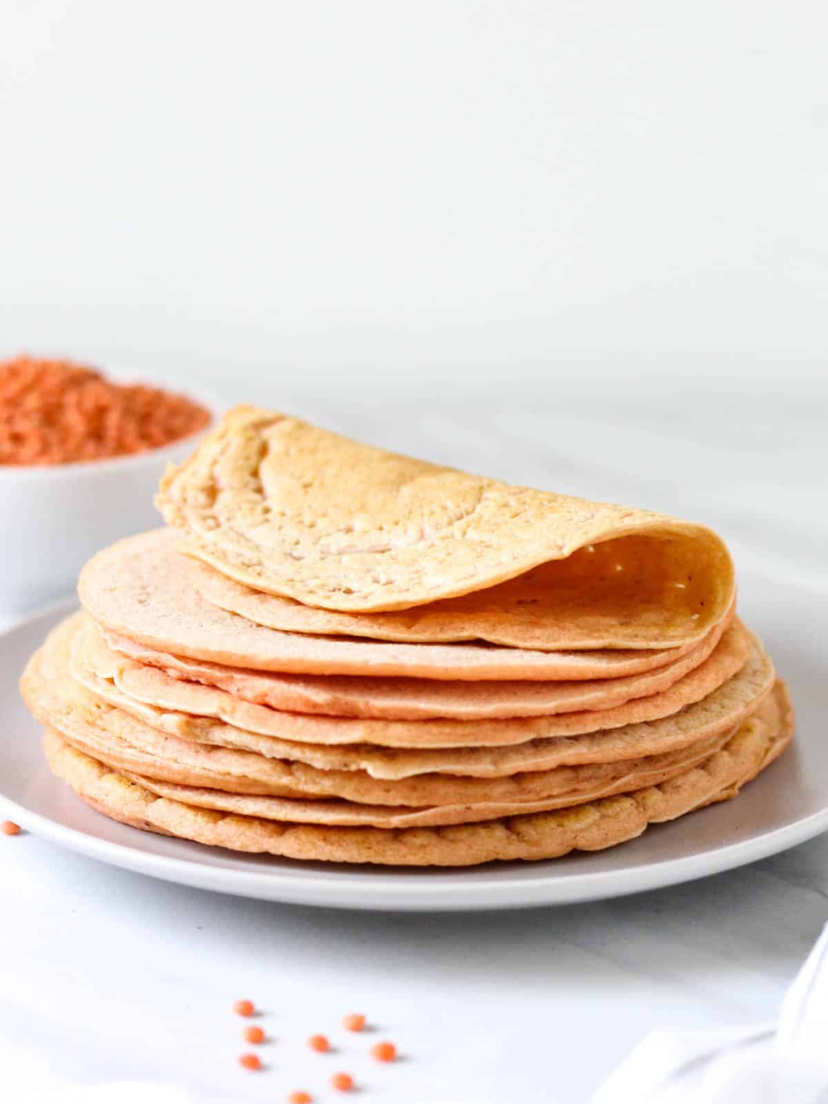 A side view of a stack of lentil tortillas on a purple plate.