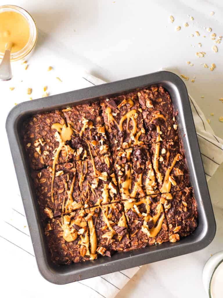 An overhead view of chocolate baked oatmeal in a black square baking pan.