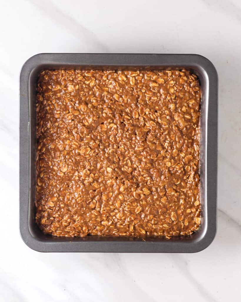 Batter of baked oats in a black square baking pan.
