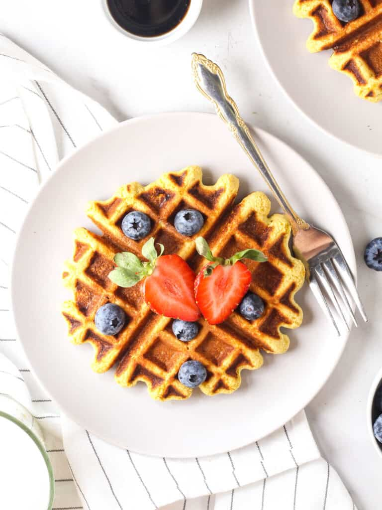 A piece of waffle served on a purple plate with a fork topped with fresh berries.