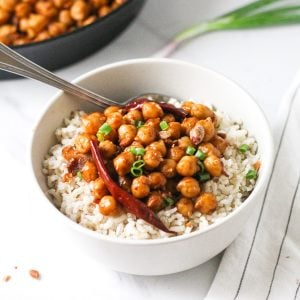 Chickpeas served on a bed of brown rice in a bowl with a spoon