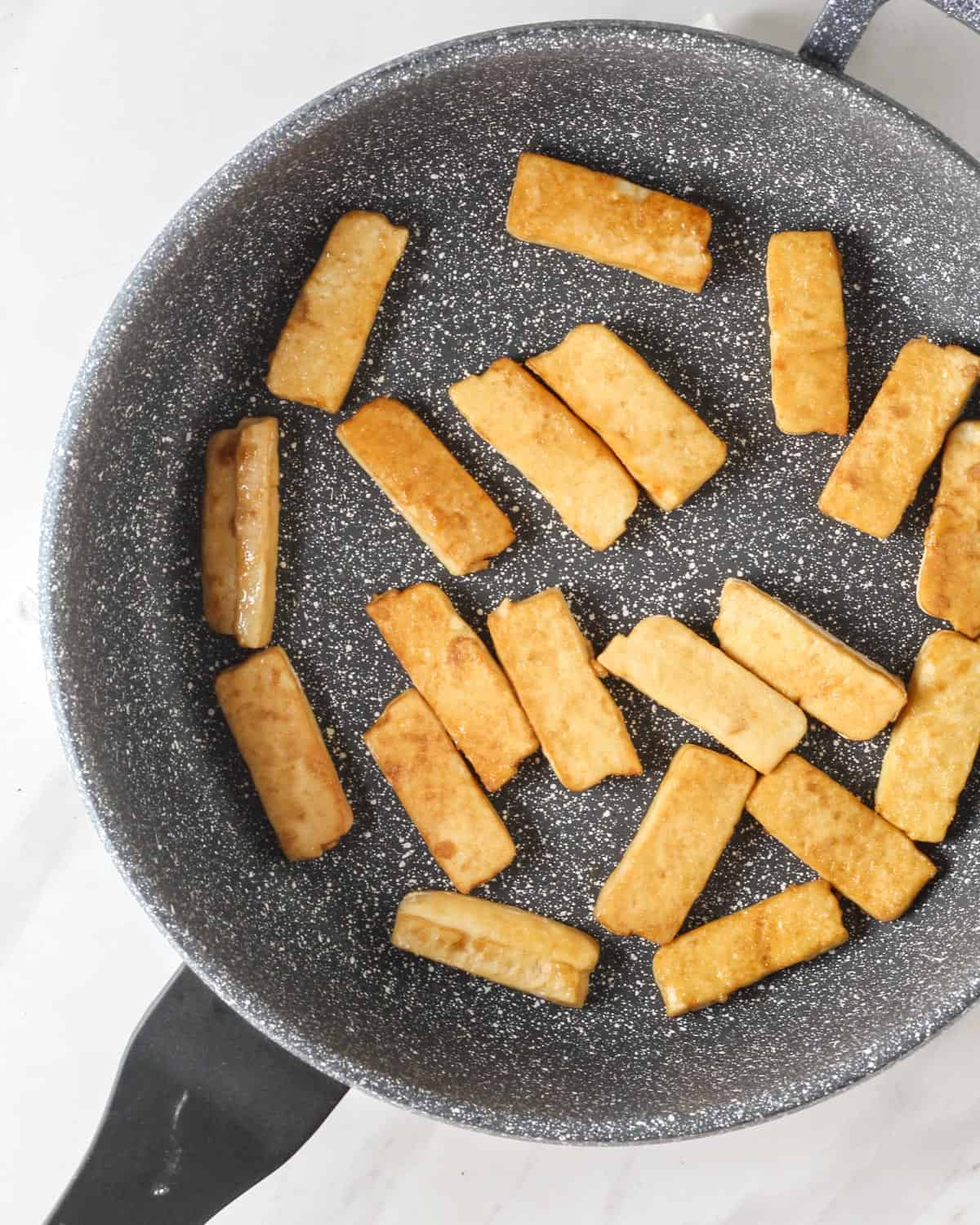 Pan-frying tofu in a pan.