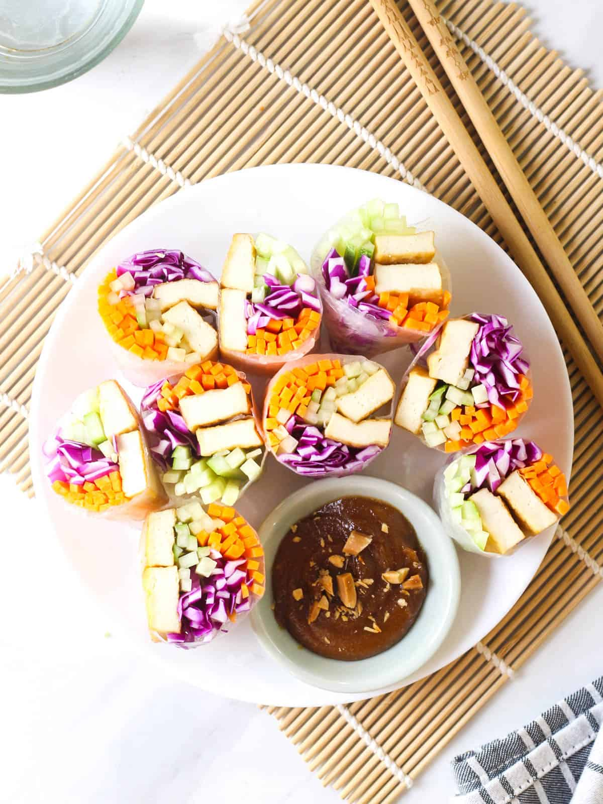 Rice paper rolls sliced into halves served on a white plate with a side of peanut sauce.