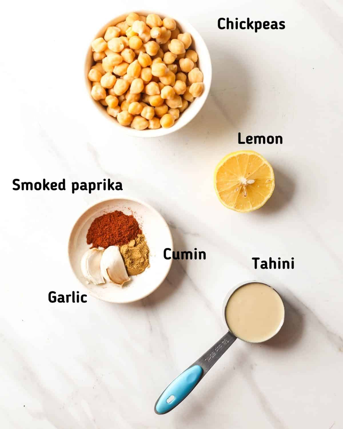 Ingredients needed for this recipe like chickpeas, tahini, paprika, garlic and cumin.