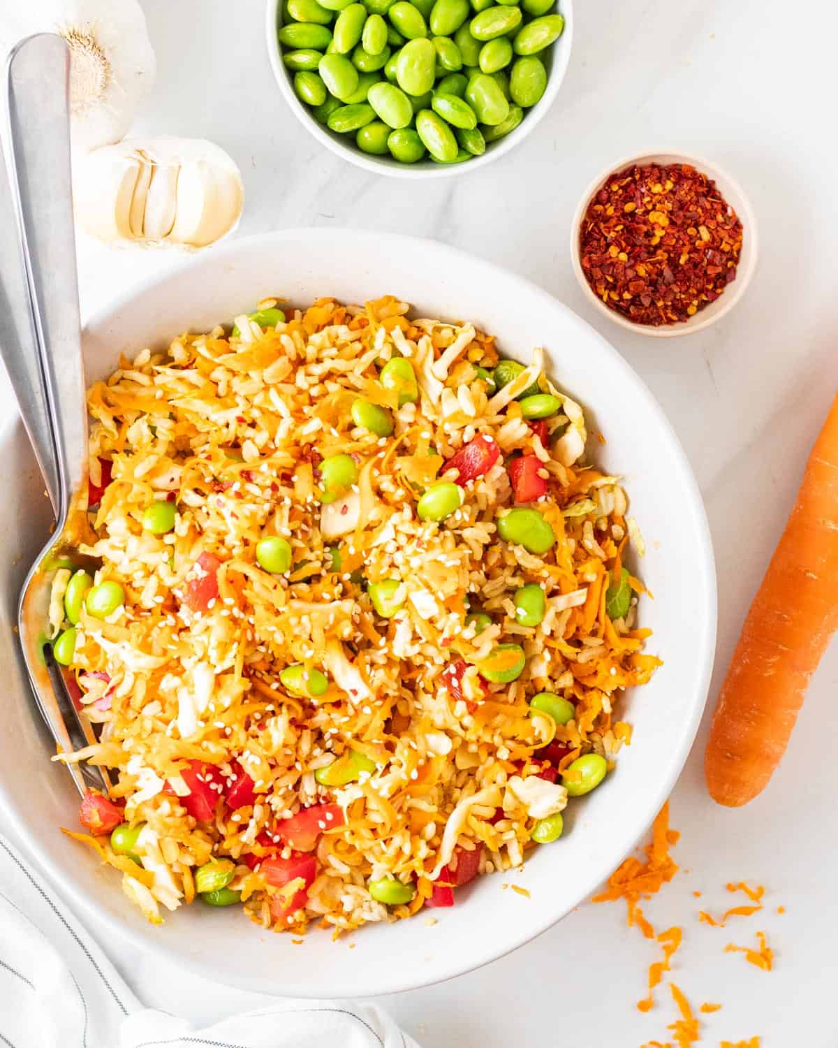Vegan rice salad served in a large bowl with fork and spoon on the side.