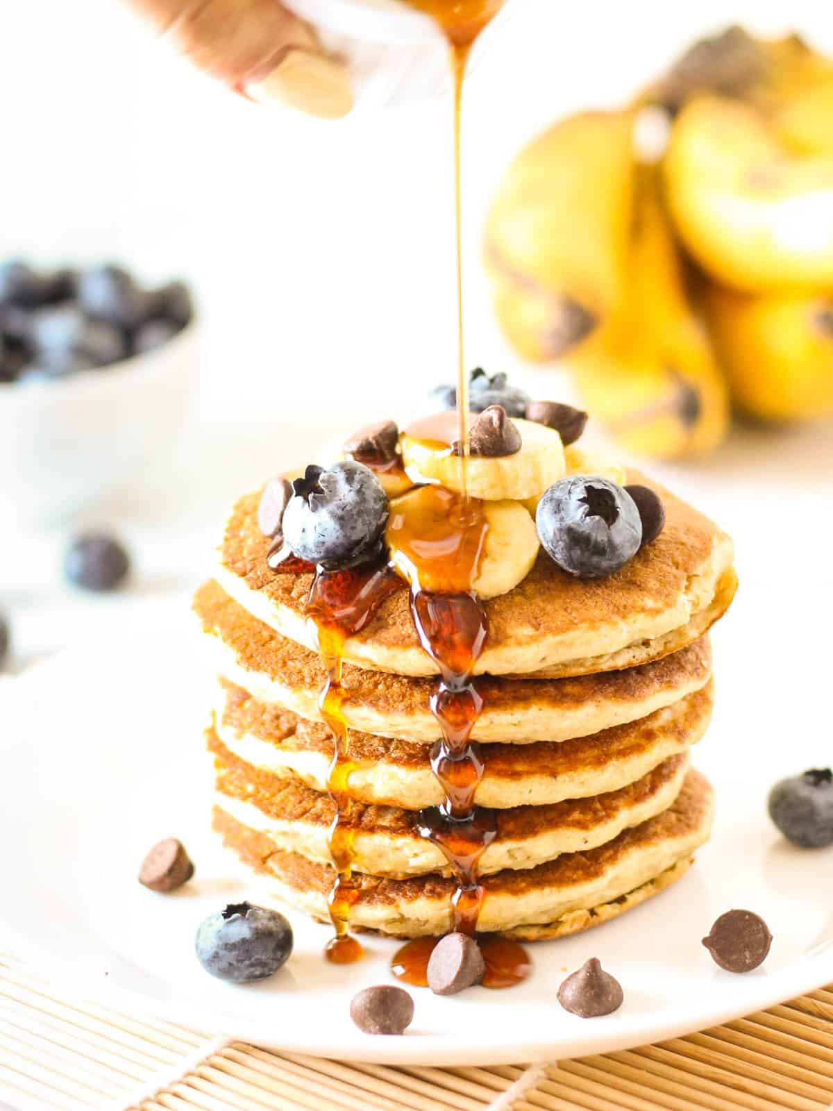 Pouring maple syrup on a stack of banana oatmeal pancakes.