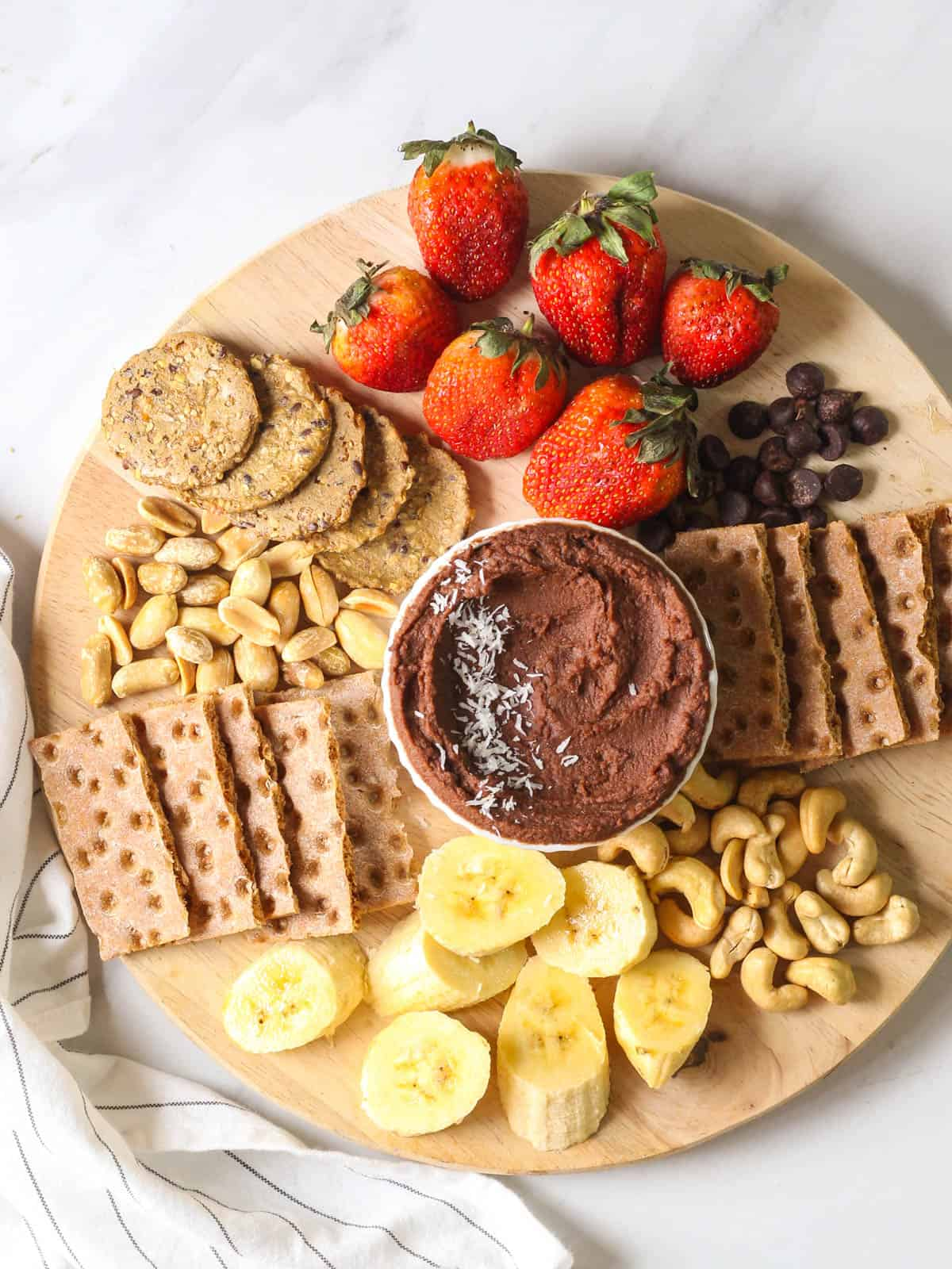 An overhead shot of vegan chocolate hummus served with fruits, nuts and crackers on a wooden chopping board.