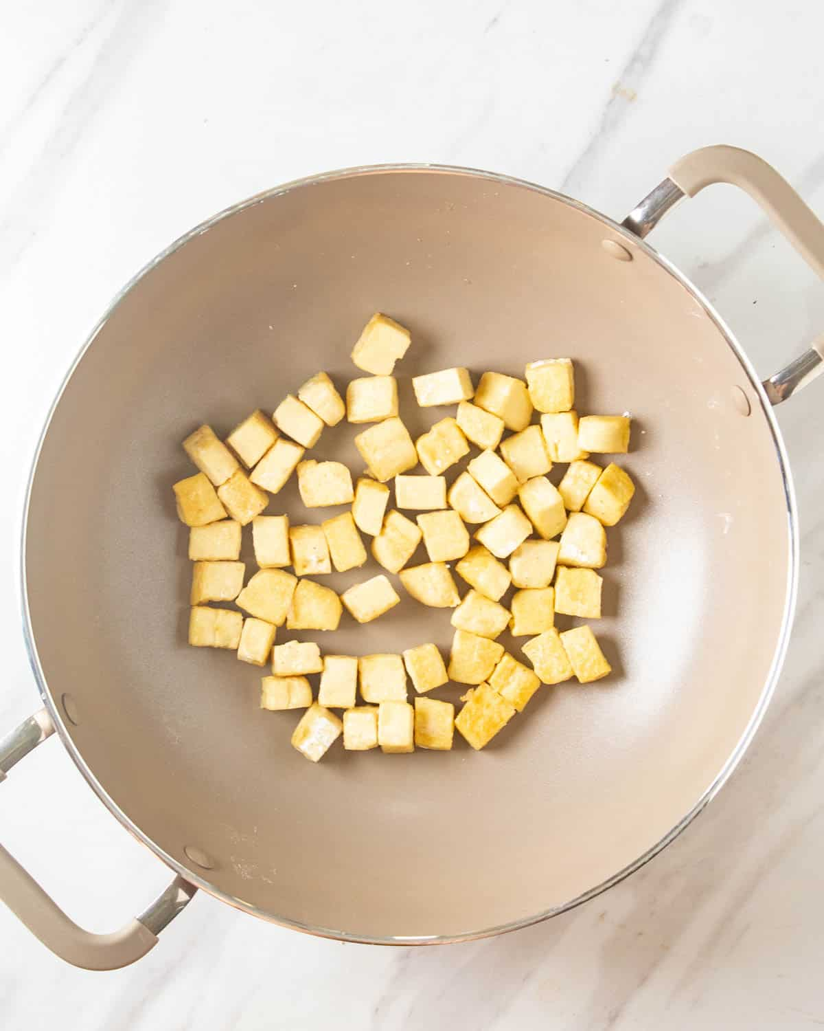 Pan frying tofu in a wok.