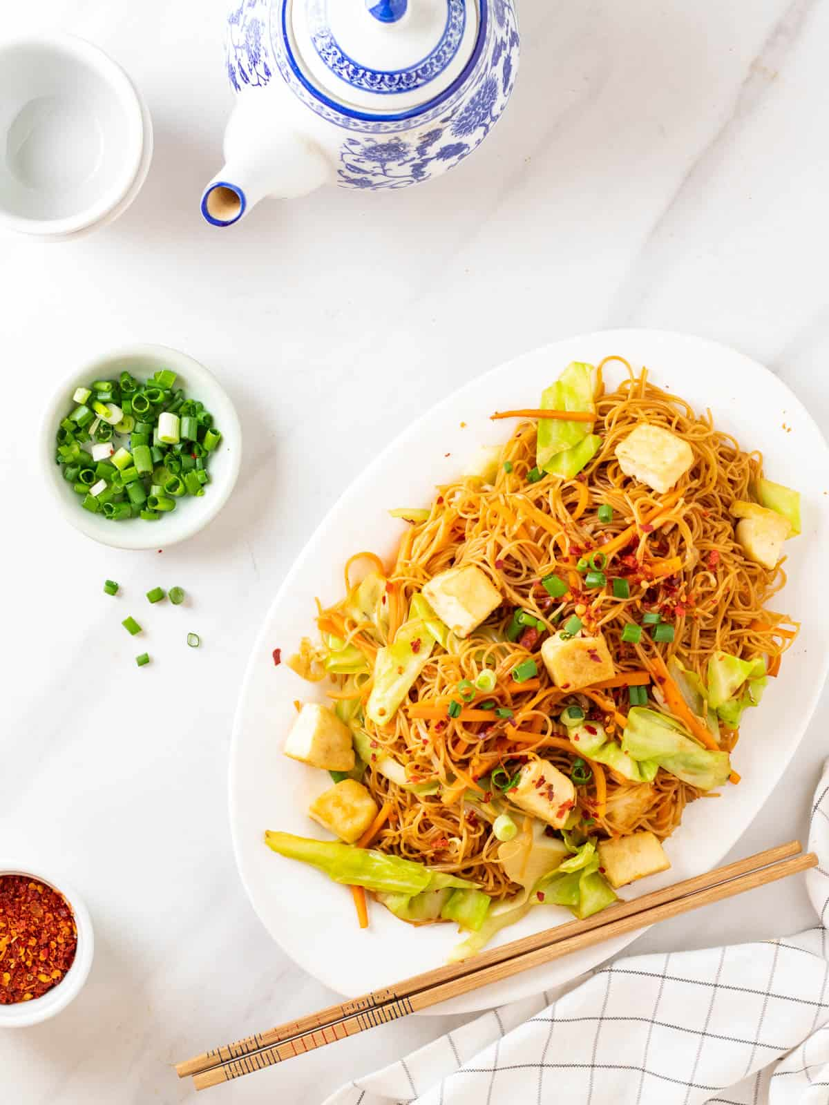 A overhead shot of fried rice vermicelli served in a white plate. There is a plate of green onion and a set of teapot in the background.
