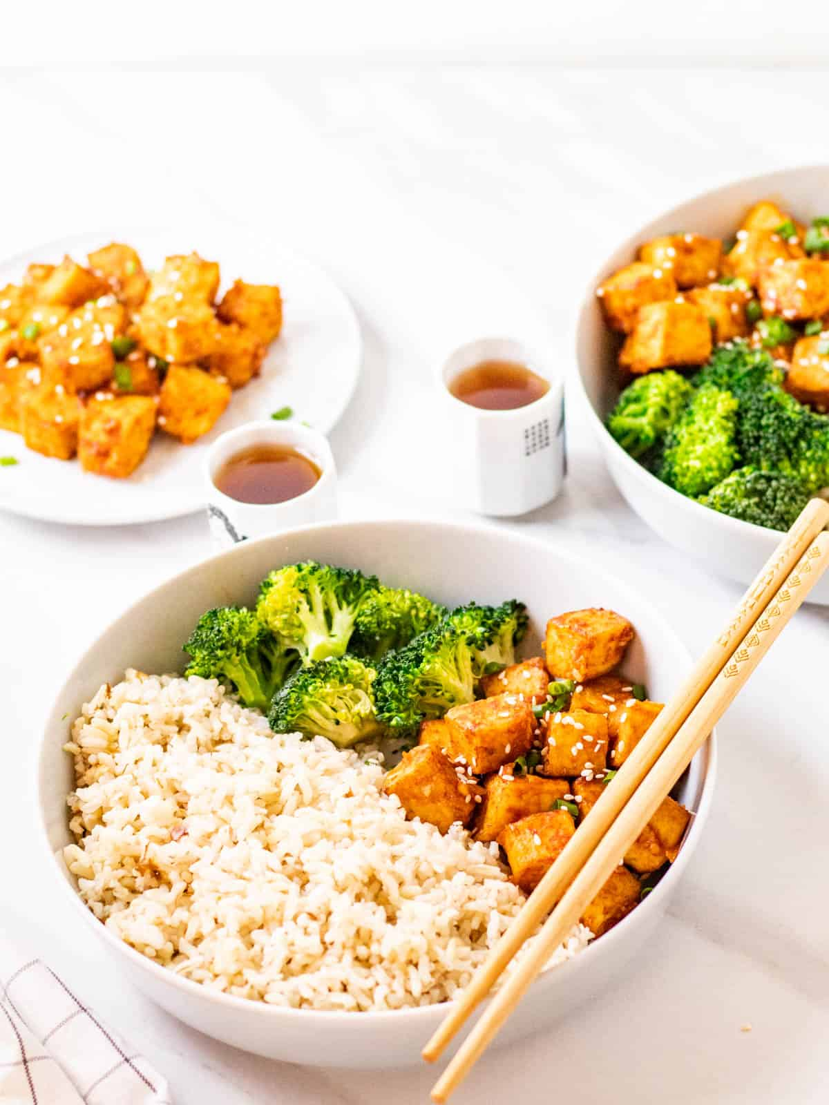 Close up shot of spicy korean tofu served with rice and broccoli with a pair of chopsticks on the side.