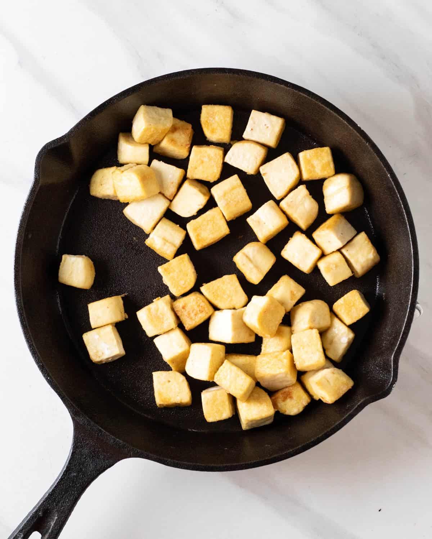 Pan frying tofu cubes in a cast iron pan.