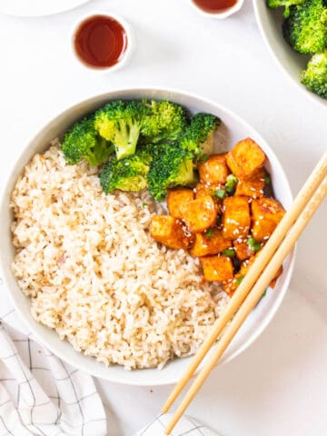 Spicy gochujang tofu served with brown rice and broccoli in a deep plate with a pair of chopsticks on the side.
