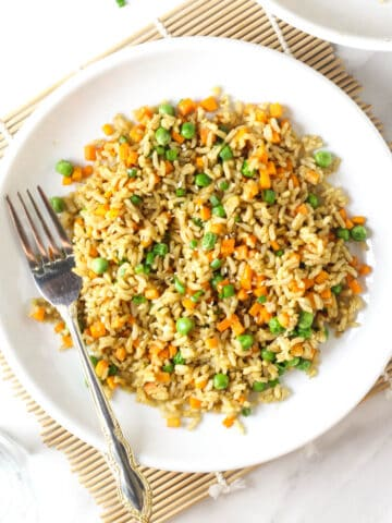 A close up of a plate of fried rice in a white plate with a fork.