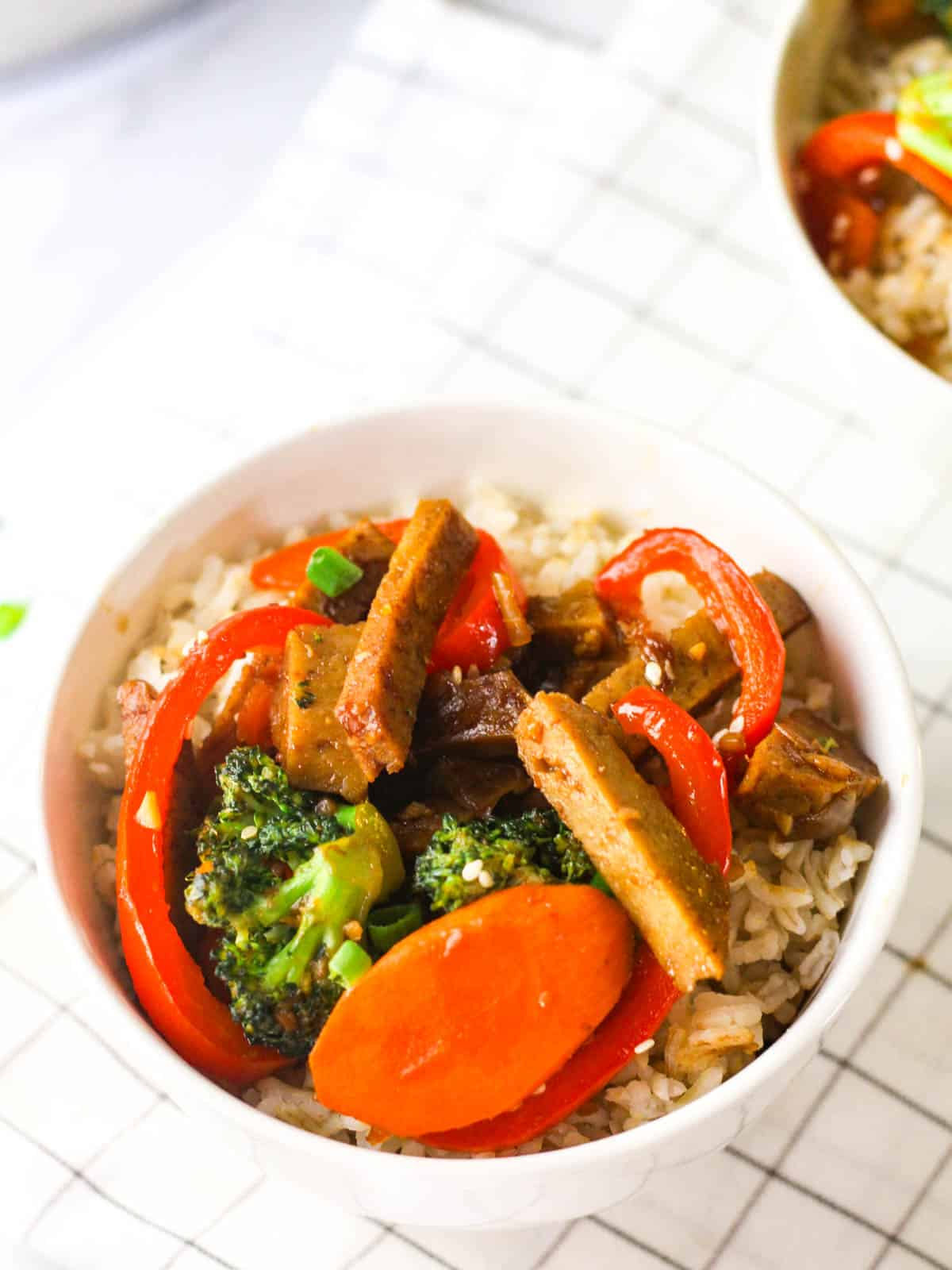 Chinese seitan stir-fry served on a bowl of rice.