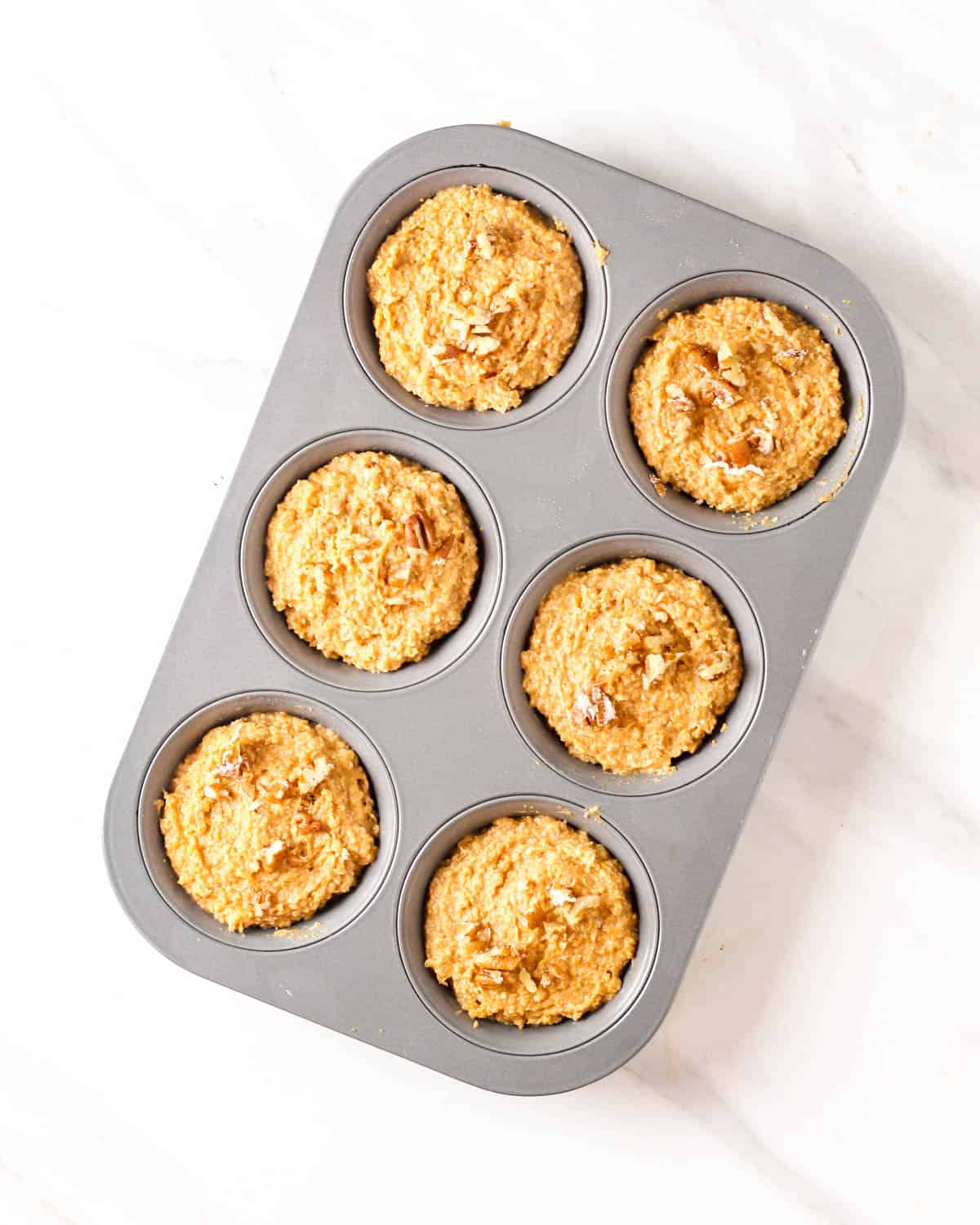 Muffin batter in a muffin pan.