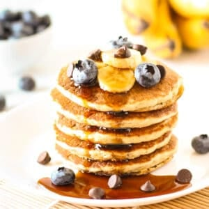 A stack of vegan banana pancakes with maple syrup drizzling down the sides.