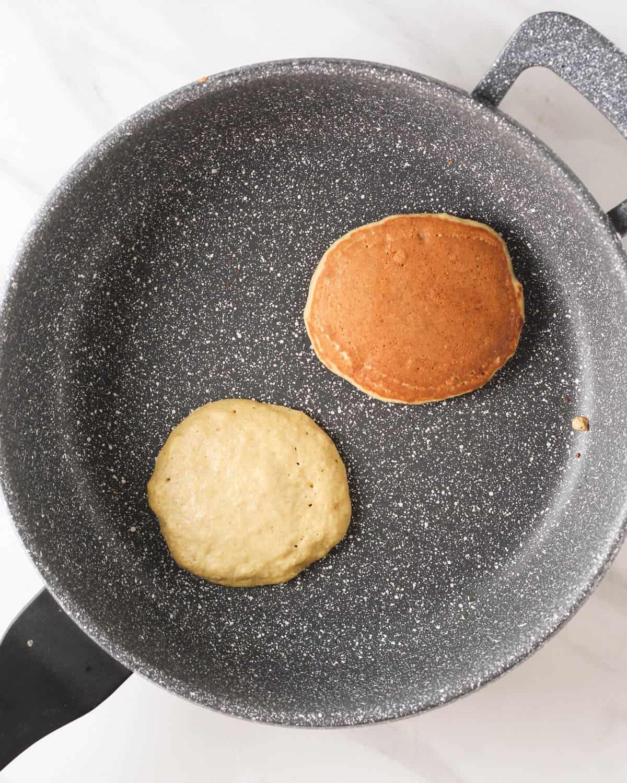 Cooking 2 pancakes in a pan.