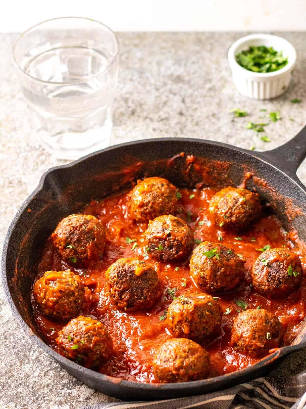 A close up of vegan tvp meatballs in a cast iron pan.