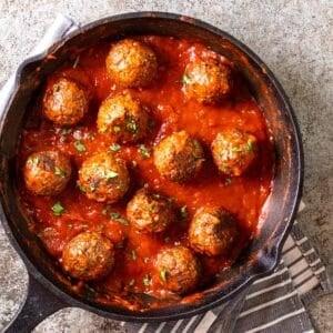 Vegan meatballs cooked in marinara sauce in a black skillet.