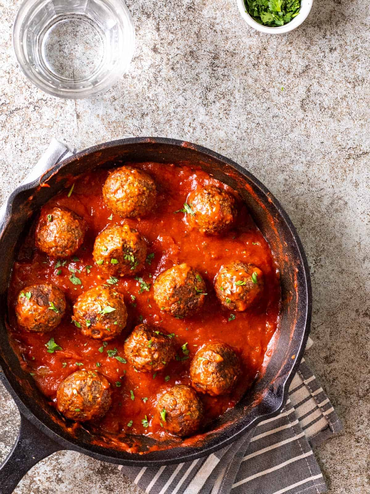 Tvp meatballs cooked with marinara sauce in a cast iron pan topped with chopped cilantro.