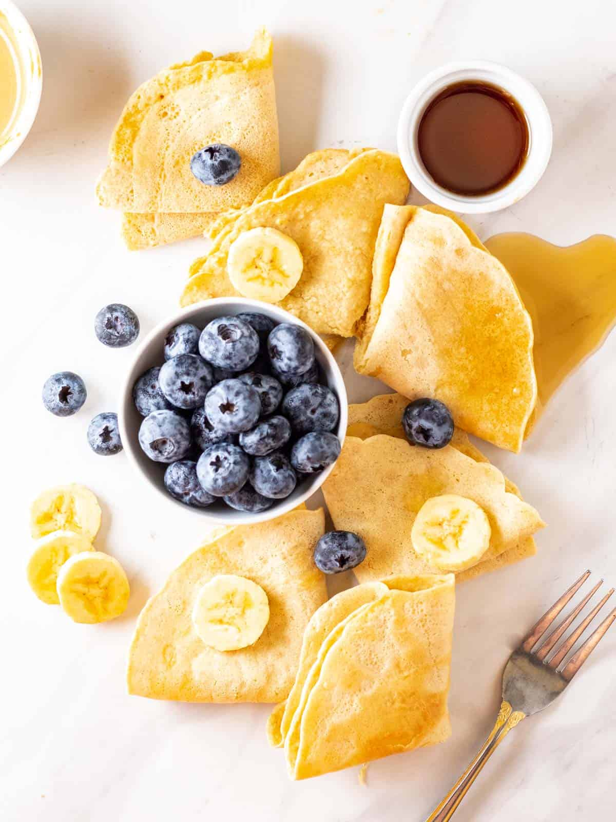 Almond milk crepes arranged on a white background with a bowl of blueberries and maple syrup.