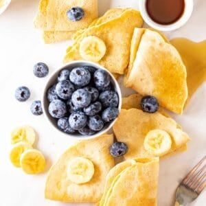 An overhead shot of almond milk crepes arranged around a bowl of blueberries.