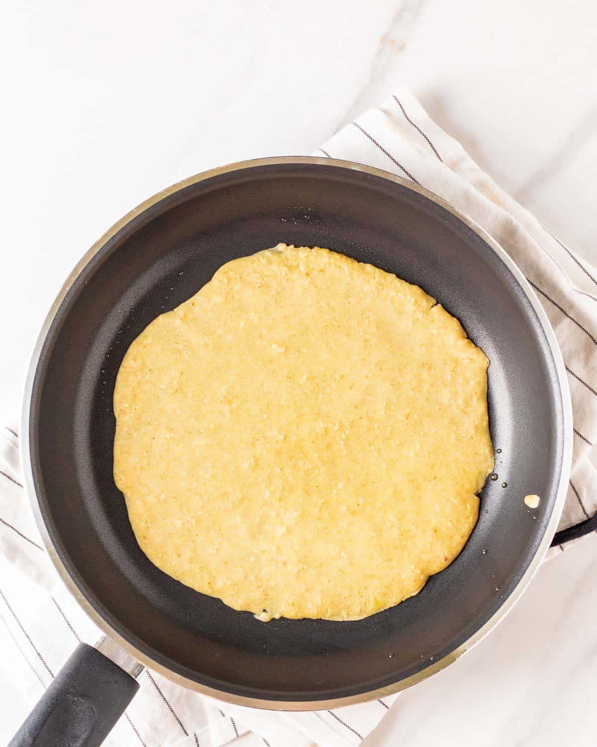 Cooking vegan crepes in a pan.