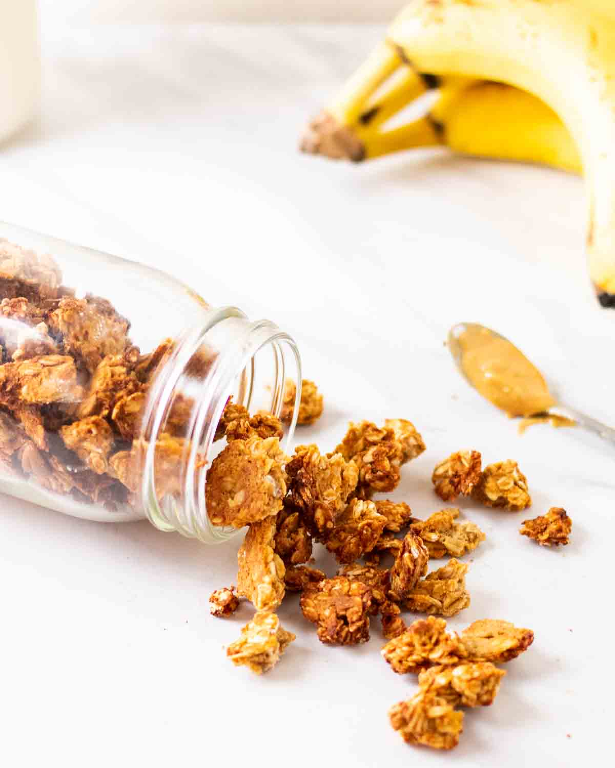 Granola spilling out of a jar with spoonful of peanut butter and banana behind.