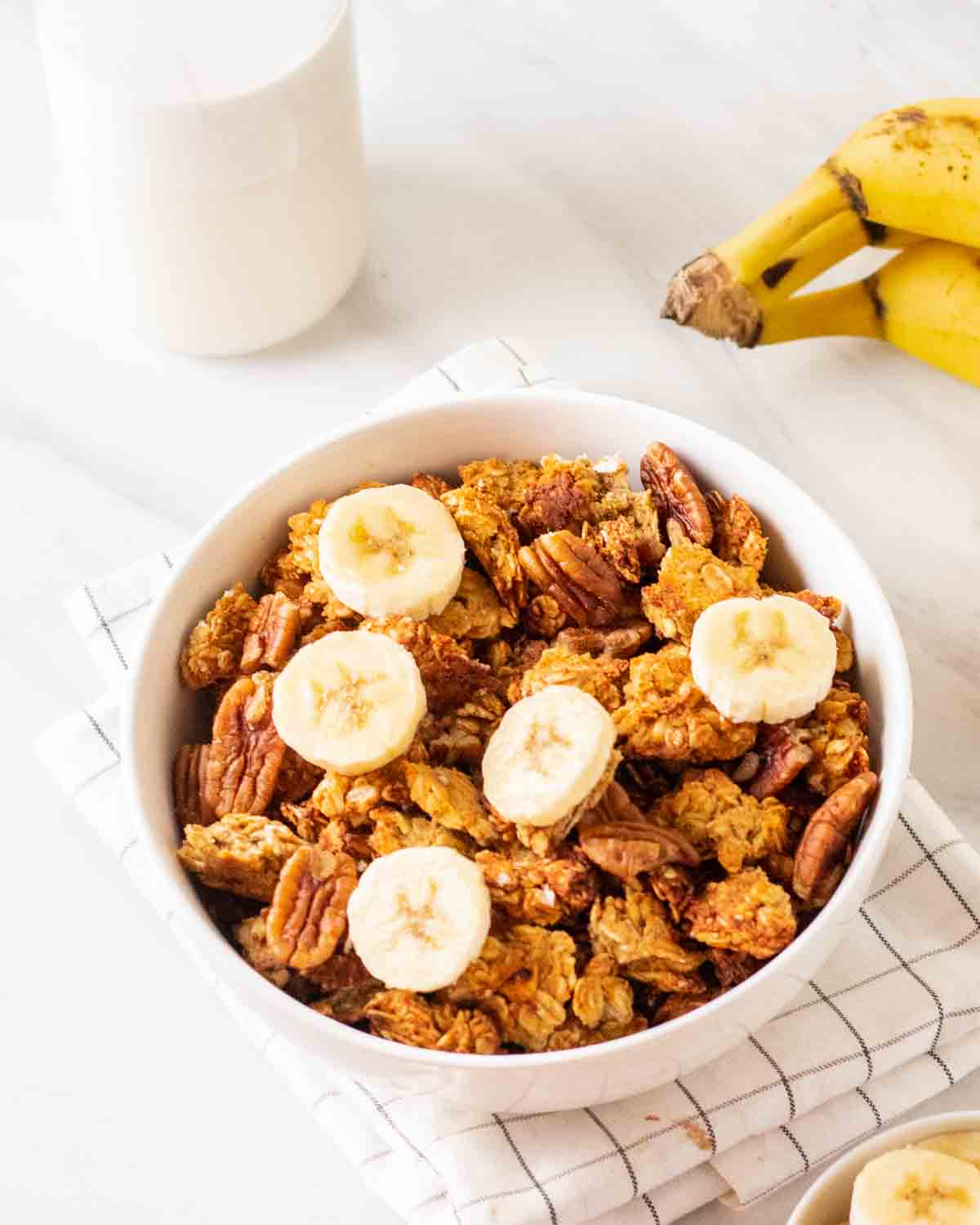 Granola in a bowl topped with sliced banana with milk and banana in the background.