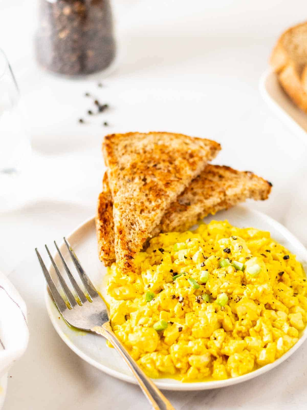 A head on shot of silken tofu scramble served with toast on a white plate.