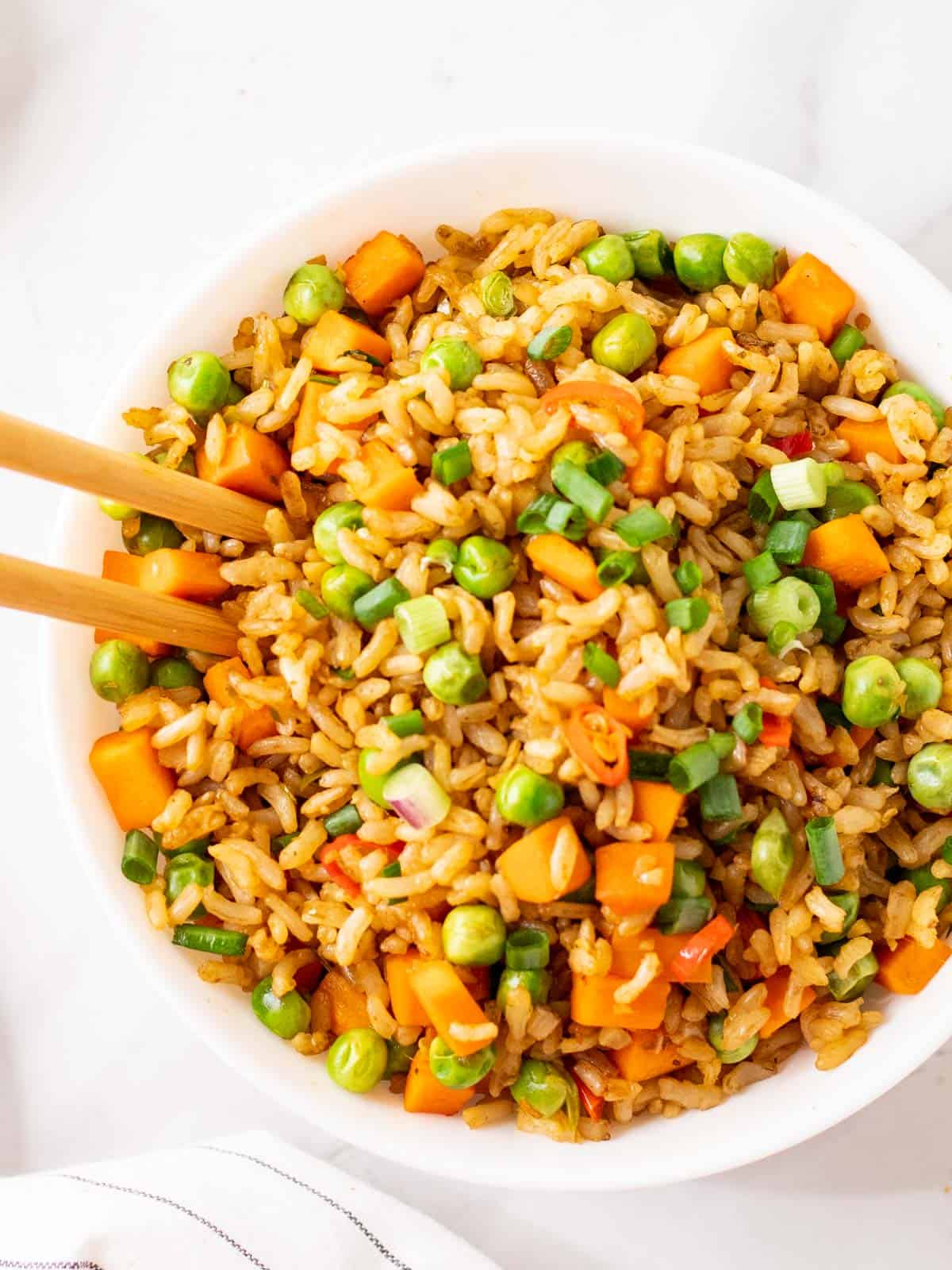 Overhead shot of vegan tom yum fried rice in a bowl with chopsticks on the side.