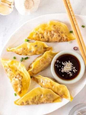 Vegan dumplings served on a plate with a pair of chopsticks on the side.