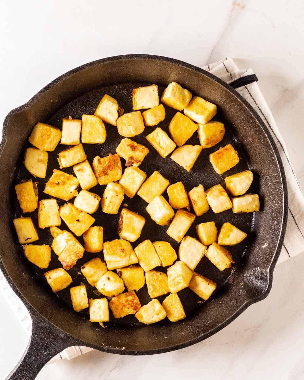 Pan fried tofu cubes in a cast iron pan.