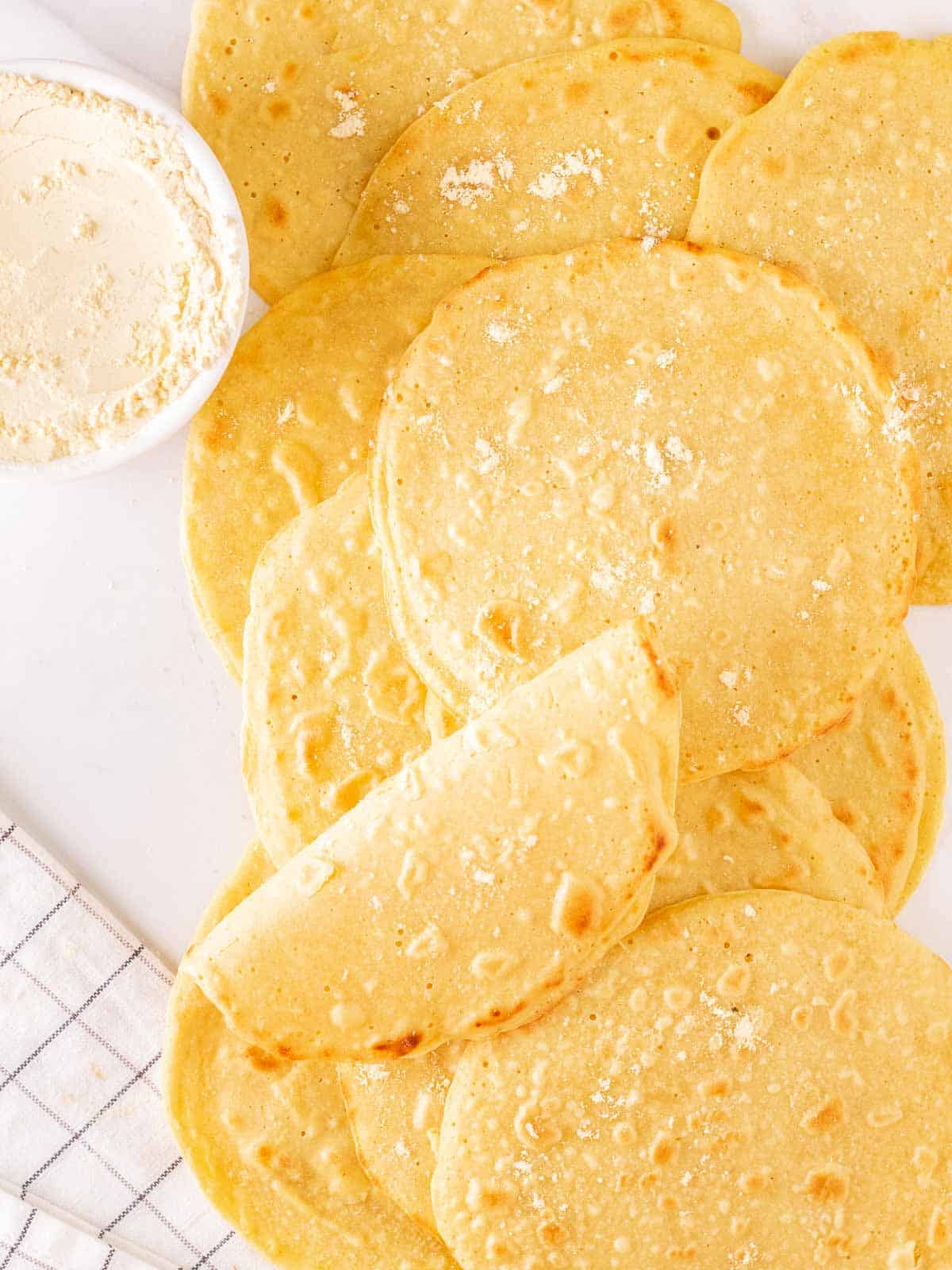 An overhead shot of chickpea flour tortillas on a white background.