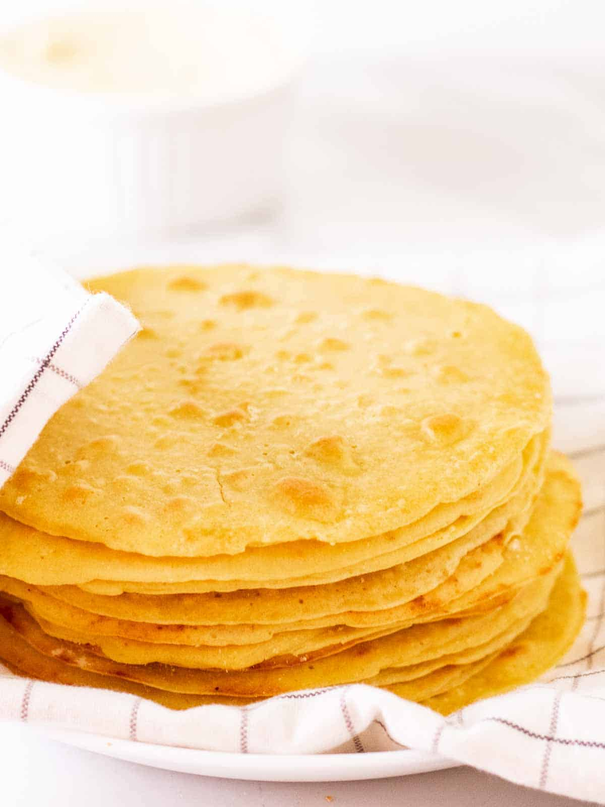 A stack of chickpea flour tortillas covered with a table cloth.