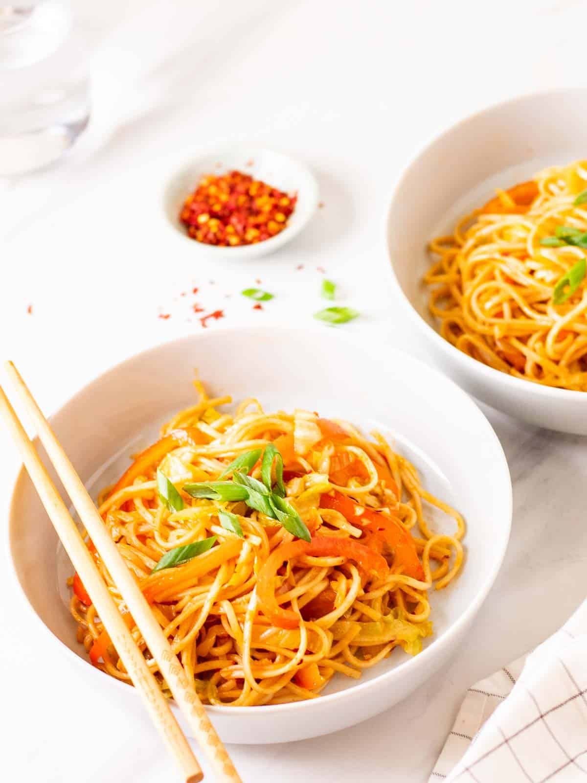 Gochujang noodles served in 2 deep plates topped with chopped green onion.