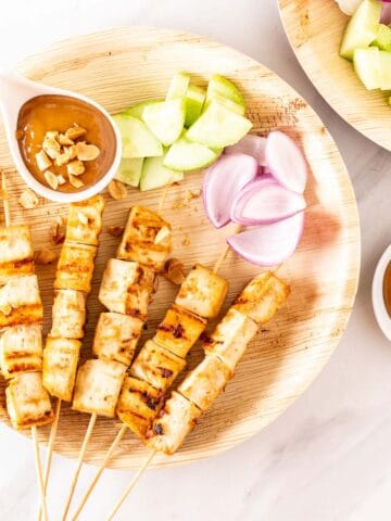 Tofu satay skewers served with peanut sauce and chopped raw vegetables.