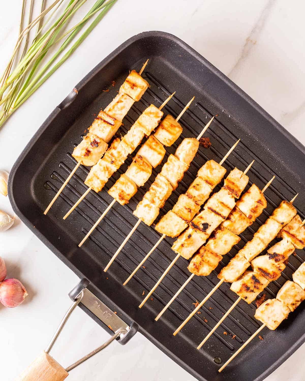 Satay skewers in a black grilling pan.