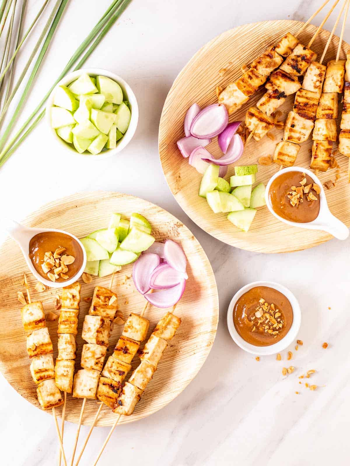 An overhead shot of 2 plates of tofu satay served with a peanut sauce, chopped cucumber and red onion.