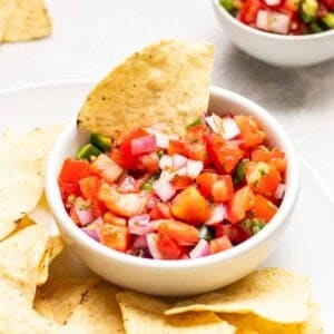 A tortilla chips dipped into a bowl of salsa.