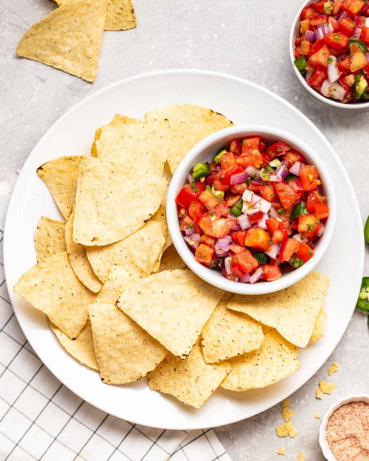 An overhead shot of salsa served with tortilla chips on a white plate.