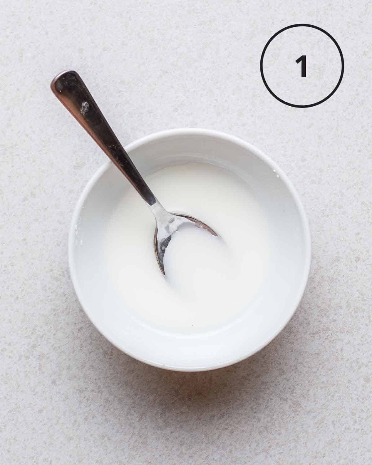cornstarch slurry in a white bowl with a spoon on a grey background.