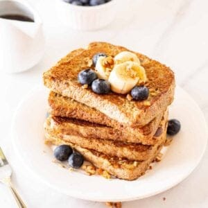 A stack of French toast served on a white plate.