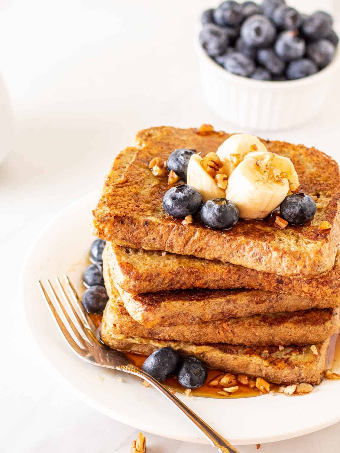A stack of French toast topped with banana slices and blueberries on a white plate with a fork.