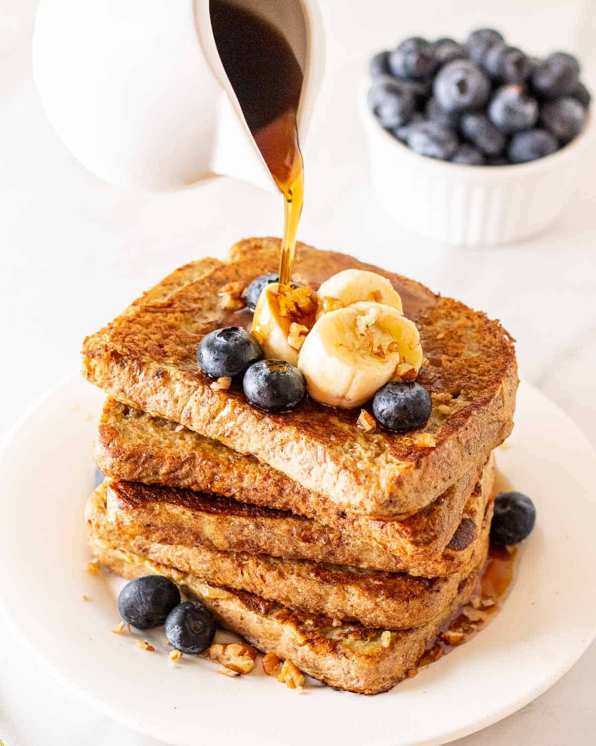 Pouring maple syrup over a stack of eggless French toast. There is a bowl of blueberries in the background.