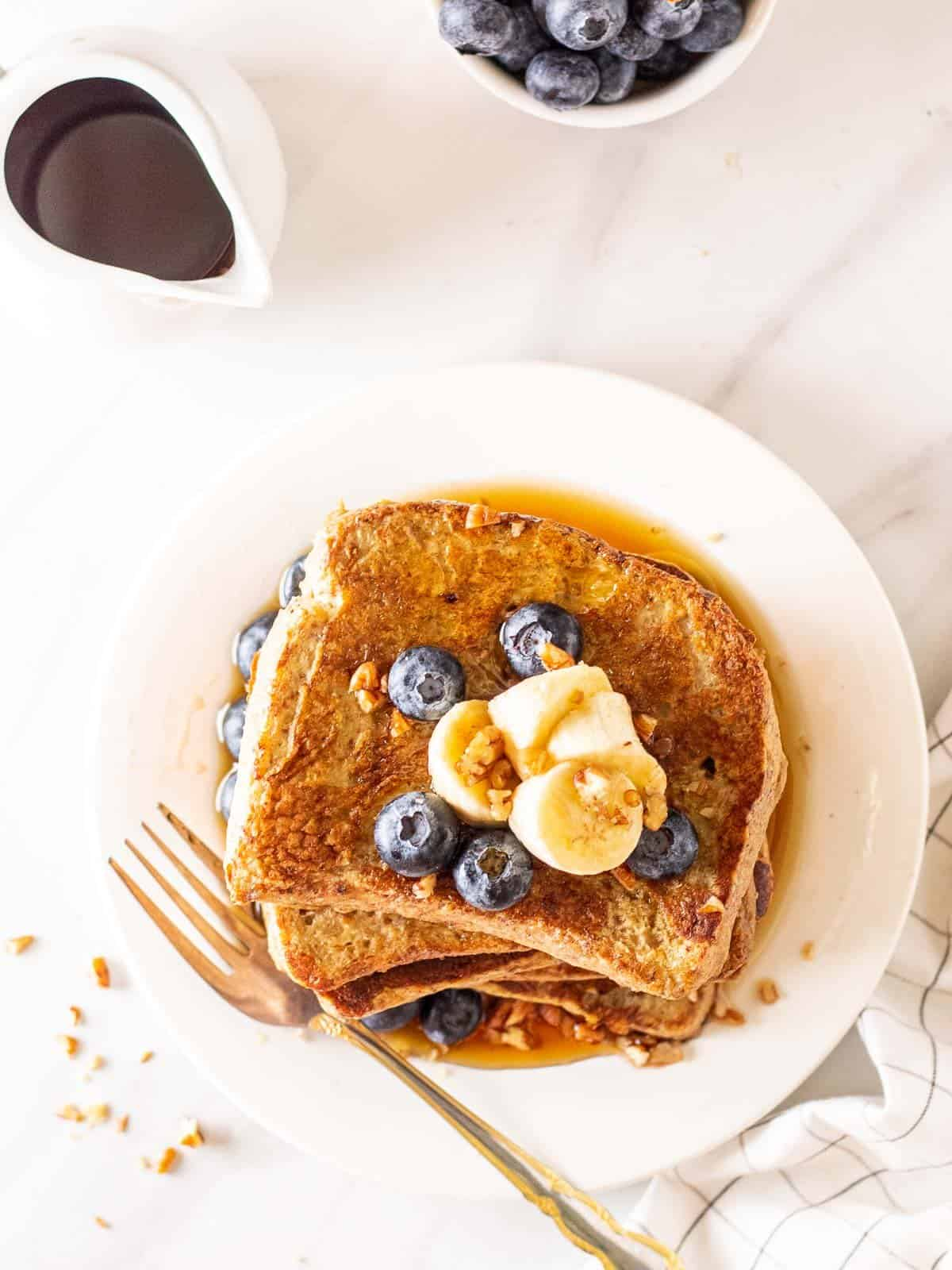 A stack of French toast served on a white plate topped with banana slices, blueberries and chopped pecans with a fork. There is a pot of maple syrup and a bowl of blueberries in the background.
