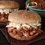 A pulled jackfruit sandwich. There is another sandwich and a bowl of pulled jackfruit in the background.