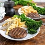 2 plates of vegan steak served with greens and fries on white plates.