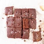 Slices of oat flour brownies arranged on a parchment paper with a small dish of flaked salt in the background.