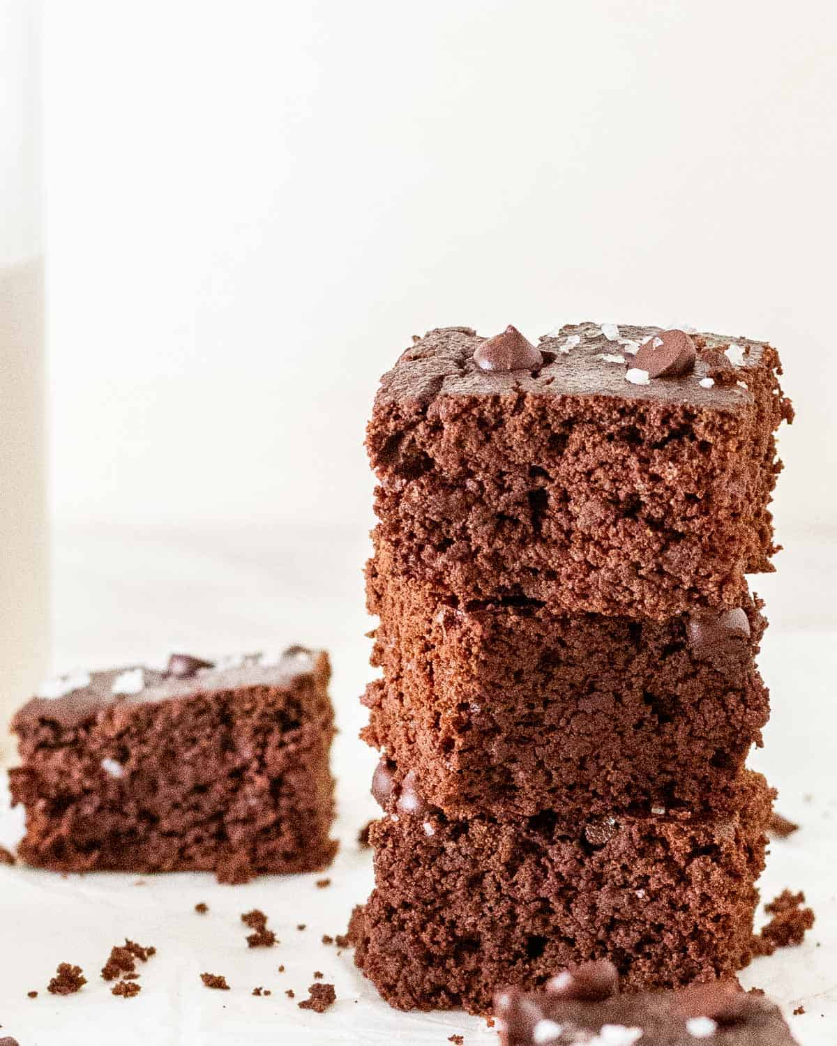 A stack of 3 brownies with a slice of brownie in the background.